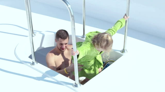 Father helps daughter to go down to the lower deck of the yacht.