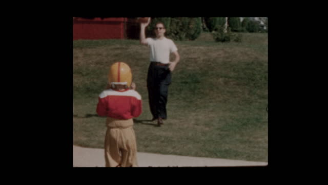 1957 Father hikes and plays football with son in football uniform