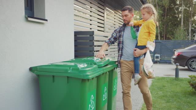 far håller en ung flicka och kommer att kasta bort en tom flaska och matavfall i papperskorgen. de använder rätt soptunnor eftersom denna familj är sortering avfall och hjälpa miljön. - gå tillsammans bildbanksvideor och videomaterial från bakom kulisserna