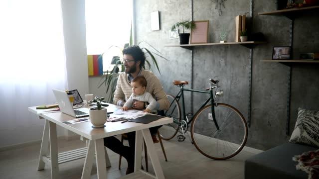 Padre que a niño y trabajando en un ordenador portátil - vídeo