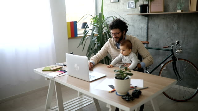 father holding baby boy and working on a laptop - padre single video stock e b–roll
