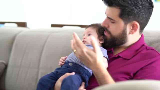 Filho de pai segurando bebê em casa - vídeo