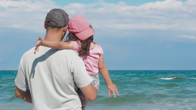 Father holding daughter and looking at sea.