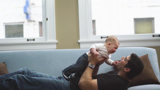 vídeos de stock e filmes b-roll de pai segurando seu filho no ar. - super baby