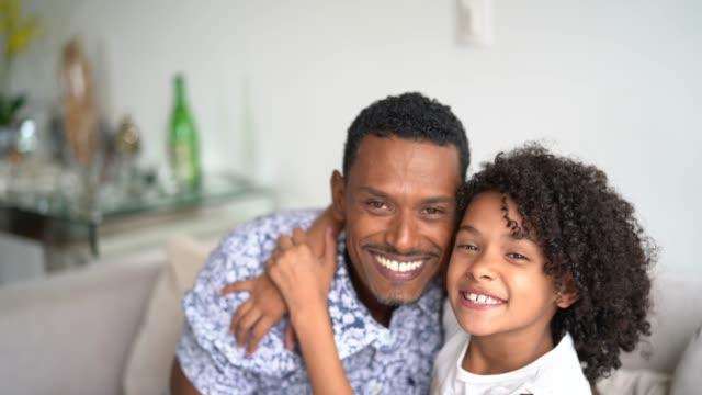 vídeos de stock, filmes e b-roll de pai que prende sua filha em casa-retrato - brasileiro pardo