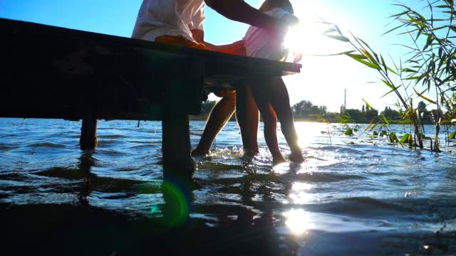 far håller i händer hans son medan du sitter på kanten av träbryggan vid sjön och dinglar benen i vattnet. lilla barnet och hans pappa svänga fötterna i floden på solig dag. slow motion närbild - flod vatten brygga bildbanksvideor och videomaterial från bakom kulisserna