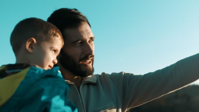 vídeos y material grabado en eventos de stock de padre hijo de sostener en sus brazos en la cima de la montaña - madre e hijos