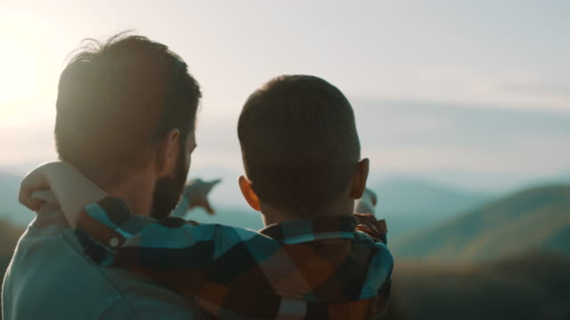 father holding son in his arms on top of the mountain - trekking video stock e b–roll