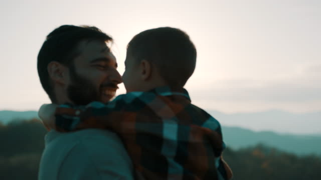 father holding son in his arms on top of the mountain - padre single video stock e b–roll