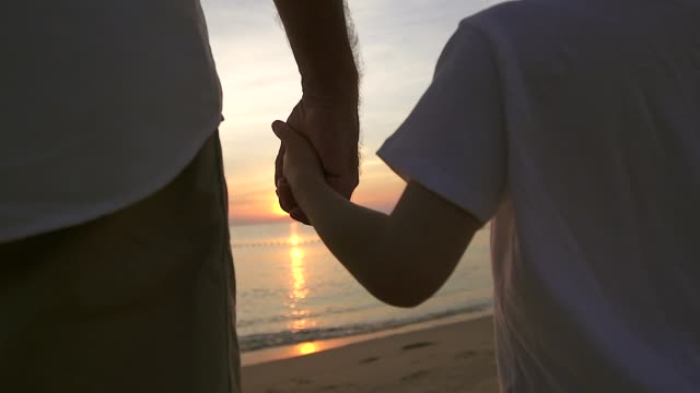 padre tenendo la mano di suo figlio che cammina sulla spiaggia all'alba, trascorrono tempo familiare di qualità insieme. - figlio maschio video stock e b–roll