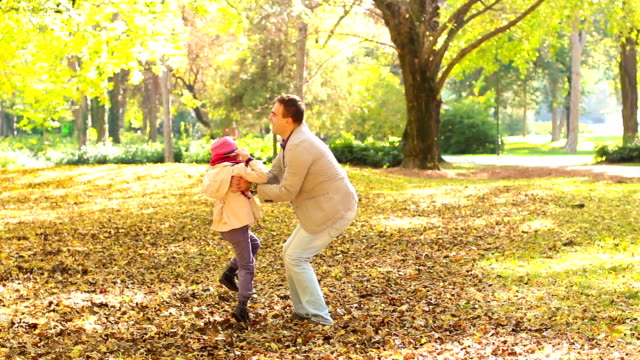 Father holding young daughter in air Father holding young daughter in air on autumn day , slow motion. swinging stock videos & royalty-free footage