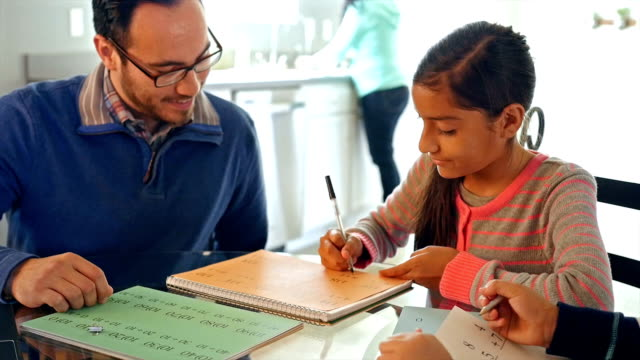 Father homeschooling his children, teaching with math worksheets video