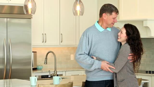 Vater umarmt erwachsene Tochter, stehend in der Küche – Video