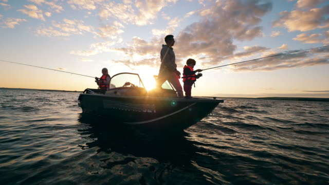 A father is helping his kids with fishing from a boat