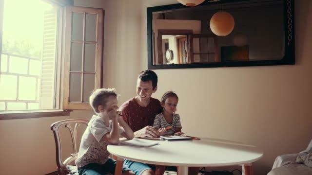 父は絵を描く子供たちと時間を過ごしている (スローモーション) - 広角撮影点の映像素材/bロール