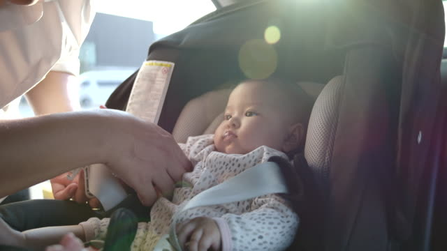 Father is taking children to sit on car seat. Flare light from the sunset 4K Slow motion, Father is taking children to sit on car seat. Flare light from the sunset seat stock videos & royalty-free footage