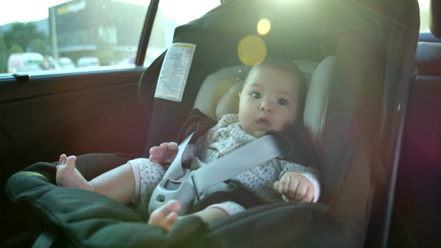 Father is taking children to sit on car seat. Flare light from the sunset 4K Slow motion, Father is taking children to sit on car seat. Flare light from the sunset land vehicle stock videos & royalty-free footage