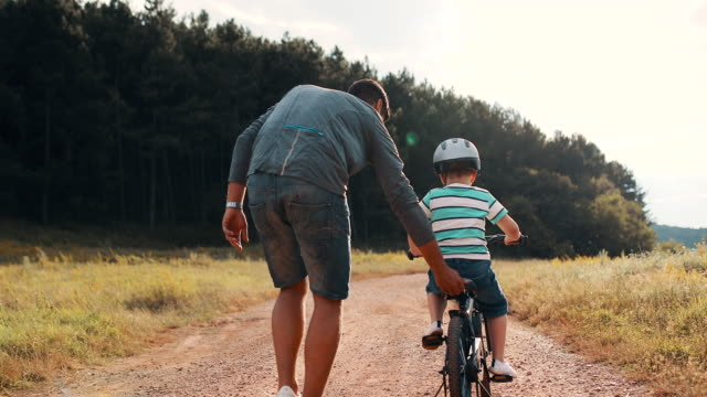 father is teaching his small son to ride bicycle in park video