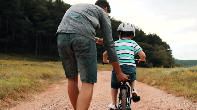 father is teaching his small son to ride bicycle in park