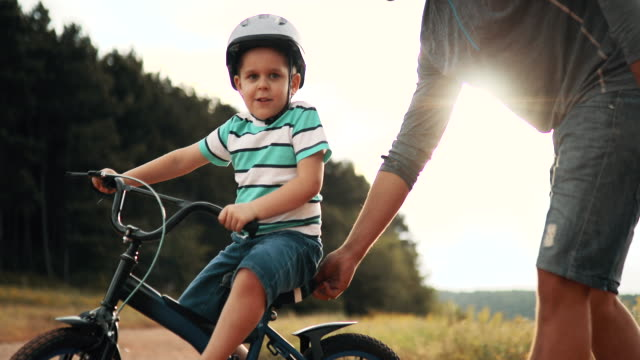 father is teaching his small son to ride bicycle in park - equilibrio video stock e b–roll