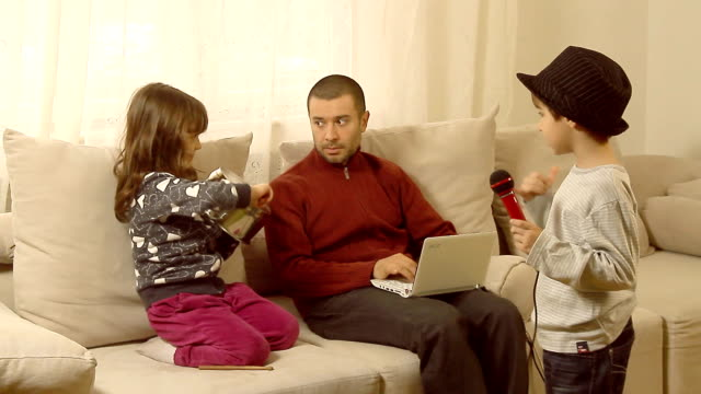 Father is trying to work,children interrupt him. video