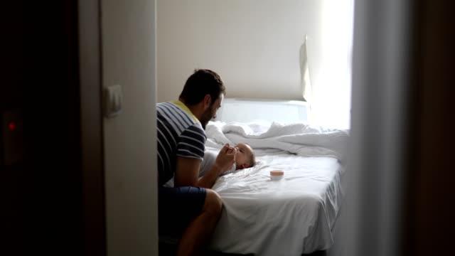 Padre besos y jugando con el bebé en un dormitorio - vídeo
