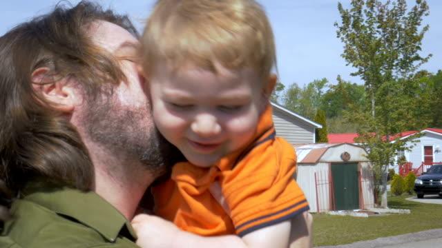 vídeos y material grabado en eventos de stock de un padre besando a su niño feliz mientras lo sostiene en sus brazos - padre que se queda en casa