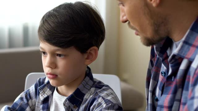 far föreläsa son, tvingar för att göra läxor, pojke tittar skyldig på pappa, närbild - parent talking to child bildbanksvideor och videomaterial från bakom kulisserna