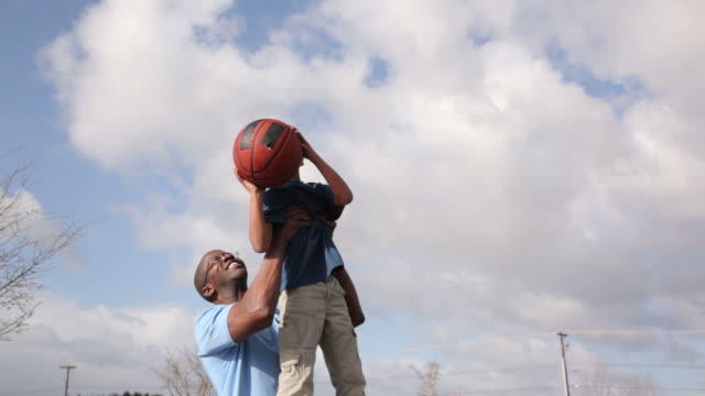 Father lifting son up to shoot basketball video