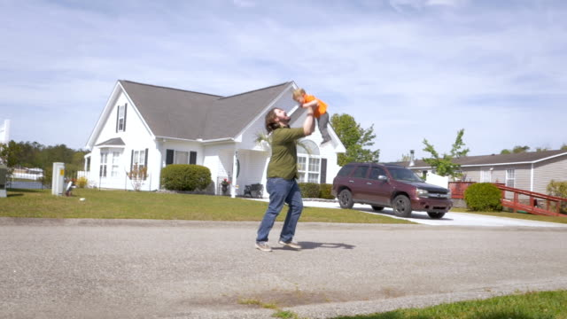 a father lovingly lifts his toddler son in the air on a street in suburbia - невинность стоковые видео и кадры b-roll