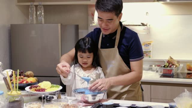 father make a sweet food with daugther - leanincollection stock videos & royalty-free footage