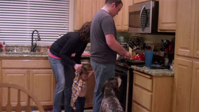 A father makes dinner while a mother undresses their little boy video