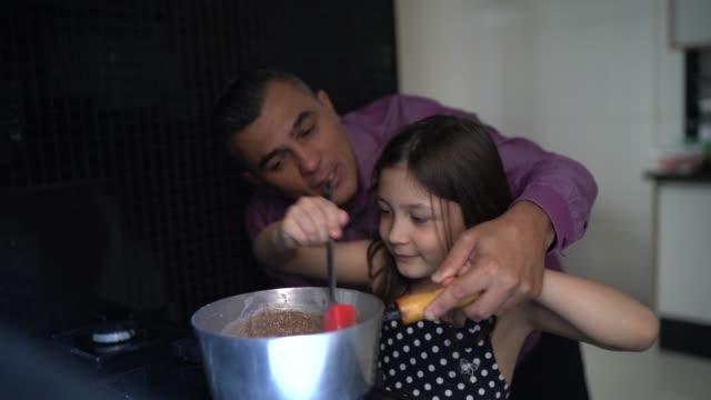 vídeos de stock, filmes e b-roll de pai fazendo chocolate com a filha em casa - brigadeiro