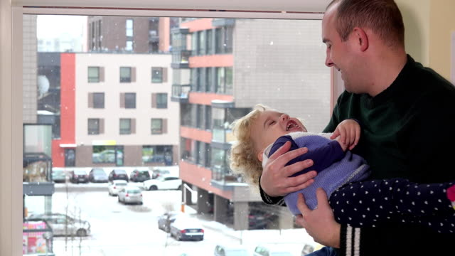 father man swing toddler daughter on his arms in front of window. Snow fall. video