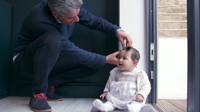 A father measures his baby daughter against a wall at home to see how tall she is