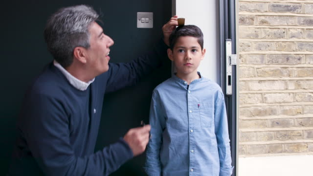 A father measures his young son against a wall to see how tall he is
