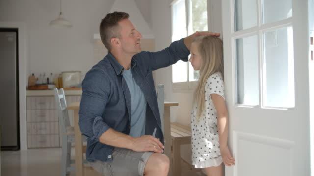 Père mesurant la hauteur de fille contre le mur - Vidéo