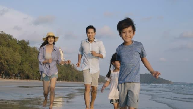 昼間に浜辺で走っている父と母と子供たち。スローモーション。家族、休日、旅行のコンセプト。 - 母娘 笑顔 日本人点の映像素材/bロール