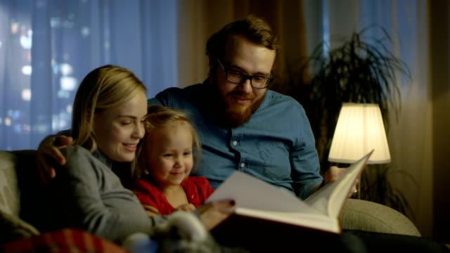 Vater, Mutter und kleinen Tochter Lesung Kinder Buch auf dem Sofa im Wohnzimmer. Es ist Abend. – Video