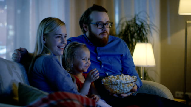 father, mother and little girl watching tv. they sit on a sofa in their cozy living room and eat popcorn. it's evening. - family home video stock e b–roll