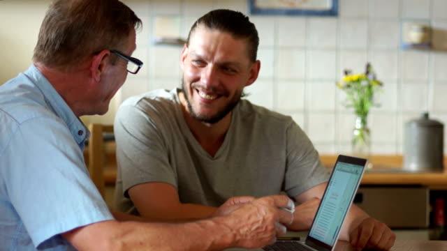Vater eines erwachsenen Sohn sprechen während der Sitzung nicht in der Küche in der Nähe des Laptops. Mein Sohn hat einen gestutzten Bart. Moderne Technologien im Leben älterer Menschen – Video
