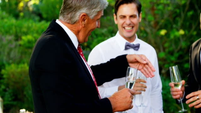 Father of the Bride toasting champagne with groom and guest 4K 4k video