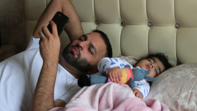 father on mobile in bed with baby - sonnecchiare video stock e b–roll