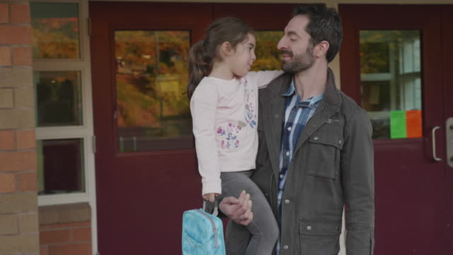 father picking his daughter up from school - padre single video stock e b–roll