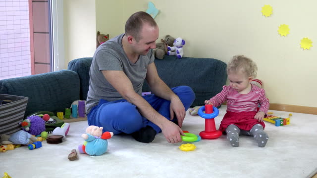 father play with baby daughter with colourful tower in room. FullHD video