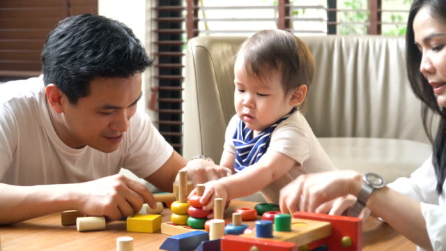 father play with his son, but he is only interested in the toy video
