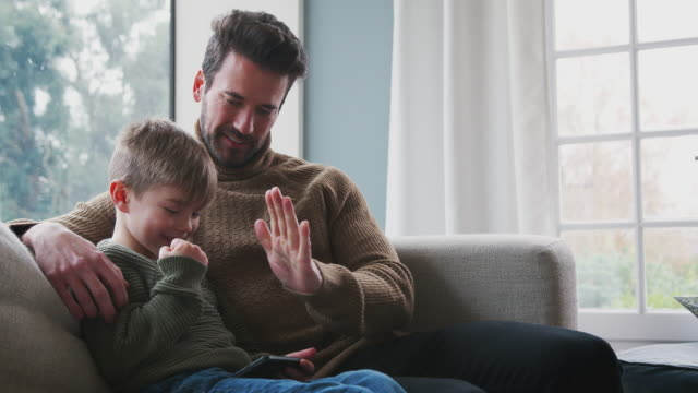 Father Playing Video Game With Son On Mobile Phone Sitting On Sofa At Home Father sitting on sofa at home with son having fun playing video game on mobile phone - shot in slow motion congratulating stock videos & royalty-free footage