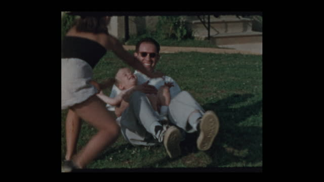 father playing with kids outside on backyard lawn - uomo nostalgia video stock e b–roll