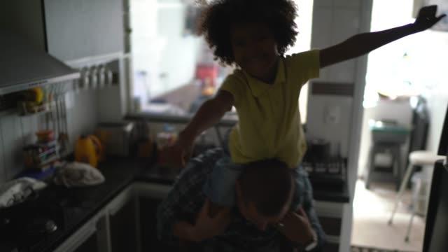 padre che gioca con il figlio in cucina - padre single video stock e b–roll