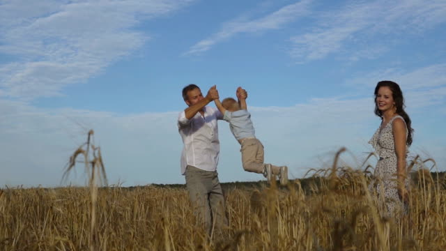 Father playing with son on the wheat field